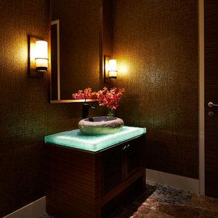 Diseño de aseo contemporáneo, de tamaño medio, con lavabo con pedestal, encimera de vidrio, paredes marrones, armarios estilo shaker y puertas de armario de madera en tonos medios