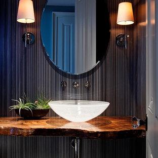 Imagen de aseo exótico con lavabo sobreencimera, paredes negras y encimeras marrones