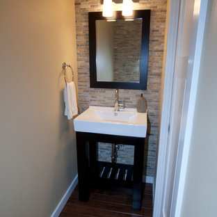 Example of a small transitional stone tile powder room design in Portland with open cabinets, dark wood cabinets, beige walls and an integrated sink