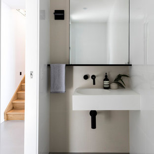 Design ideas for a modern powder room in Sunshine Coast with beige tile, concrete floors, an integrated sink, grey floor and white benchtops.