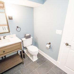 ニューヨークの中くらいのトランジショナルスタイルのおしゃれなトイレ・洗面所 (青い壁、レイズドパネル扉のキャビネット、中間色木目調キャビネット、一体型トイレ、スレートの床、アンダーカウンター洗面器、人工大理石カウンター) の写真