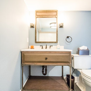 This is an example of a medium sized traditional cloakroom in New York with blue walls, raised-panel cabinets, medium wood cabinets, a one-piece toilet, slate flooring, a submerged sink and solid surface worktops.