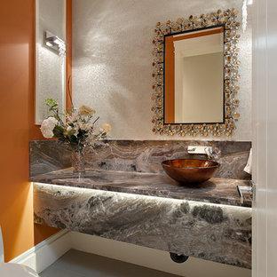 Imagen de aseo actual, pequeño, con lavabo sobreencimera, encimera de mármol, sanitario de dos piezas, baldosas y/o azulejos grises, parades naranjas, suelo de baldosas de porcelana y losas de piedra