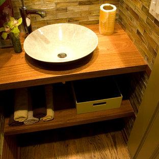Удачное сочетание для дизайна помещения: маленький туалет в современном стиле с настольной раковиной, разноцветной плиткой, стеклянной плиткой и паркетным полом среднего тона - самое интересное для вас