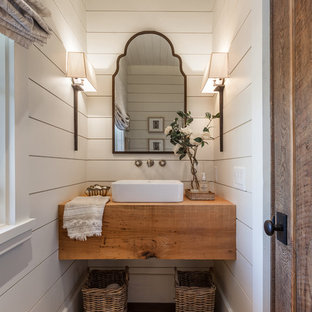 Inspiration for a beach style dark wood floor powder room remodel in Atlanta with white walls, a vessel sink, wood countertops and brown countertops