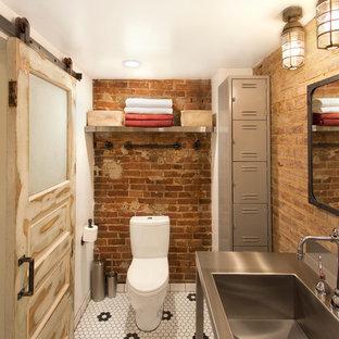 Idéer för ett industriellt toalett, med bänkskiva i rostfritt stål, en toalettstol med separat cisternkåpa, mosaikgolv, ett integrerad handfat och svart och vit kakel