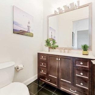 Пример оригинального дизайна: маленький туалет в стиле шебби-шик с фасадами с выступающей филенкой, темными деревянными фасадами, раздельным унитазом, белыми стенами, полом из керамогранита, накладной раковиной, столешницей из искусственного кварца, черным полом и белой столешницей