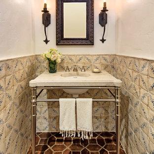 Esempio di un piccolo bagno di servizio mediterraneo con piastrelle multicolore, piastrelle in ceramica, pareti bianche, pavimento in terracotta, top in superficie solida, pavimento marrone e lavabo a consolle