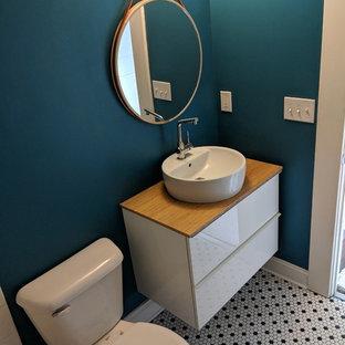 На фото: туалет среднего размера в стиле ретро с плоскими фасадами, белыми фасадами, раздельным унитазом, синими стенами, полом из мозаичной плитки, настольной раковиной, столешницей из дерева, разноцветным полом и коричневой столешницей с
