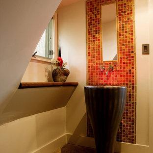На фото: туалет среднего размера в современном стиле с раковиной с пьедесталом, красной плиткой, плиткой мозаикой и бетонным полом с