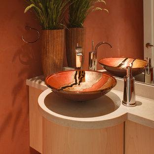 На фото: туалет в современном стиле с настольной раковиной, плоскими фасадами и светлыми деревянными фасадами с