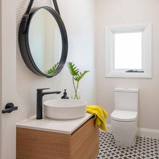 Стильный дизайн: туалет среднего размера в современном стиле с унитазом-моноблоком, белой плиткой, плиткой мозаикой, белыми стенами, полом из цементной плитки, настольной раковиной, столешницей из искусственного кварца, белой столешницей, плоскими фасадами, фасадами цвета дерева среднего тона и разноцветным полом - последний тренд