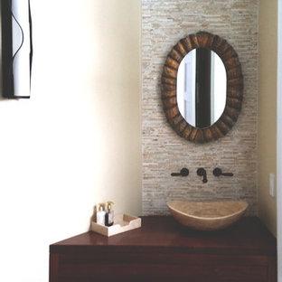 Cette photo montre un petit WC et toilettes tendance avec des portes de placard marrons, un carrelage beige, un mur beige, une vasque, un plan de toilette en bois, un carrelage de pierre, un sol en bois foncé, un sol marron et un plan de toilette marron.