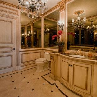 Ispirazione per un grande bagno di servizio classico con ante con bugna sagomata, ante in legno chiaro, WC a due pezzi, piastrelle a specchio, pareti beige, pavimento in gres porcellanato, lavabo sottopiano, top in marmo e pavimento beige