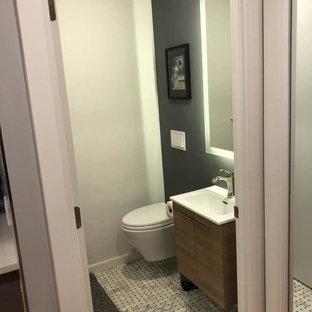 Kleine Moderne Gästetoilette mit flächenbündigen Schrankfronten, hellbraunen Holzschränken, weißer Wandfarbe, Marmorboden, integriertem Waschbecken, Quarzwerkstein-Waschtisch, grauem Boden, weißer Waschtischplatte und Wandtoilette in New York