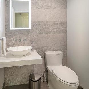 Foto di un piccolo bagno di servizio design con WC monopezzo, piastrelle beige, piastrelle di cemento, pareti beige, pavimento in laminato, lavabo a bacinella, top in marmo, pavimento beige e top bianco