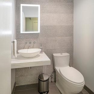 Esempio di un piccolo bagno di servizio design con WC monopezzo, piastrelle beige, piastrelle di cemento, pareti beige, pavimento in laminato, lavabo a bacinella, top in marmo, pavimento beige e top bianco