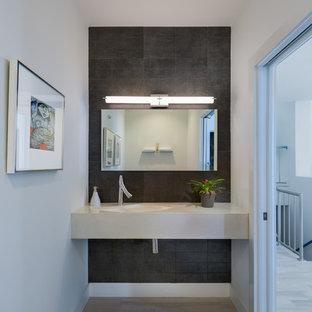 Idee per un bagno di servizio moderno di medie dimensioni con piastrelle grigie, piastrelle in ceramica, pareti bianche, pavimento in vinile, top in quarzo composito e top beige