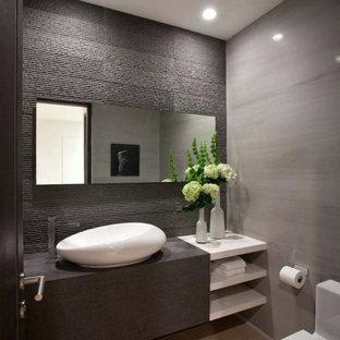 Modelo de aseo actual, de tamaño medio, con armarios con paneles lisos, puertas de armario marrones, sanitario de una pieza, paredes grises, lavabo sobreencimera, suelo beige y encimeras marrones