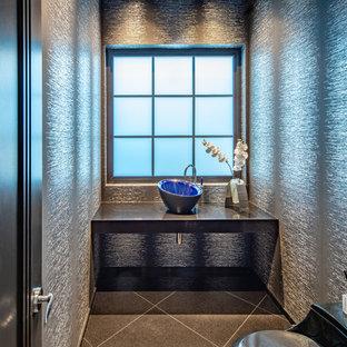 Cette image montre un petit WC et toilettes design avec un placard sans porte, un WC à poser, un mur noir, un sol en marbre, une vasque, un plan de toilette en surface solide, un sol noir et un plan de toilette noir.