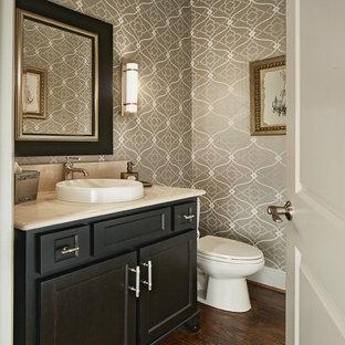 На фото: туалет в классическом стиле с фасадами с утопленной филенкой, темными деревянными фасадами, керамической плиткой, темным паркетным полом, мраморной столешницей, коричневыми стенами, настольной раковиной, коричневым полом и бежевой столешницей с