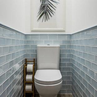 Diseño de aseo marinero con baldosas y/o azulejos azules, baldosas y/o azulejos de cerámica, suelo de baldosas de cerámica, sanitario de dos piezas y paredes blancas