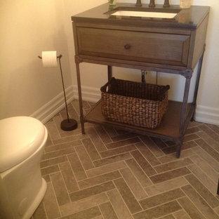 Klassisk inredning av ett mellanstort toalett, med möbel-liknande, skåp i mellenmörkt trä, en toalettstol med hel cisternkåpa, beige väggar, klinkergolv i keramik, ett undermonterad handfat och brunt golv