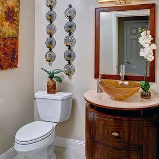 Свежая идея для дизайна: туалет в стиле современная классика с настольной раковиной, фасадами островного типа, темными деревянными фасадами, столешницей из известняка, раздельным унитазом, бежевыми стенами и полом из керамогранита - отличное фото интерьера