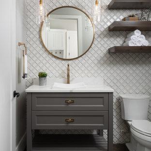 Réalisation d'un WC et toilettes tradition avec un placard avec porte à panneau encastré, des portes de placard grises, un carrelage blanc, un sol en bois foncé, une vasque, un sol marron, un plan de toilette blanc et meuble-lavabo sur pied.
