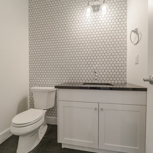 This is an example of a small traditional powder room in Edmonton with recessed-panel cabinets, white cabinets, a two-piece toilet, white tile, porcelain tile, white walls, vinyl floors, a drop-in sink, quartzite benchtops and white floor.