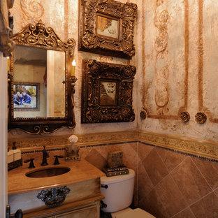 Inspiration pour un WC et toilettes victorien de taille moyenne avec un placard à porte plane, des portes de placard en bois vieilli, un WC séparé, un carrelage marron, des carreaux de céramique, un mur marron et un lavabo encastré.