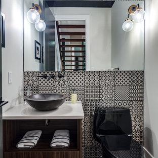 Moderne Gästetoilette mit offenen Schränken, hellbraunen Holzschränken, Wandtoilette mit Spülkasten, schwarz-weißen Fliesen, Mosaikfliesen, braunem Holzboden, Aufsatzwaschbecken, braunem Boden und weißer Waschtischplatte in Calgary