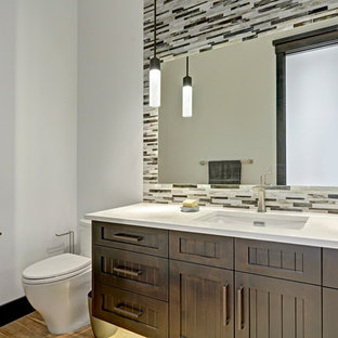 Photo of a medium sized traditional cloakroom in Calgary with shaker cabinets, dark wood cabinets, a one-piece toilet, multi-coloured tiles, white walls, porcelain flooring, a built-in sink and quartz worktops.