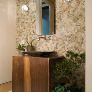 Contemporary cloakroom in Los Angeles with a vessel sink, medium wood cabinets, wooden worktops, multi-coloured tiles, pebble tiles and brown worktops.
