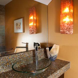 Пример оригинального дизайна интерьера: туалет в стиле модернизм с настольной раковиной, плоскими фасадами, темными деревянными фасадами и столешницей из переработанного стекла