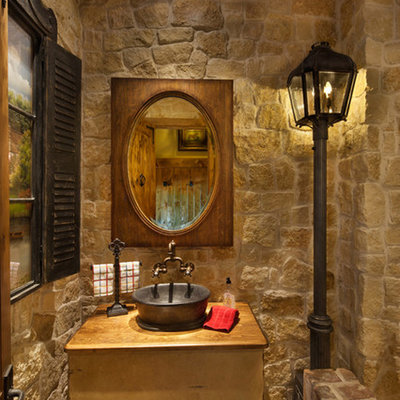 Example of a mid-sized tuscan beige tile and stone tile brick floor and beige floor powder room design in Dallas with open cabinets, a vessel sink, wood countertops, light wood cabinets, a two-piece toilet, beige walls and brown countertops