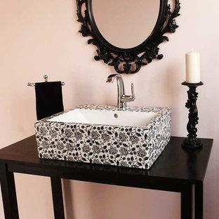 Cette photo montre un petit WC et toilettes éclectique avec un mur rose, une vasque, un placard en trompe-l'oeil, des portes de placard noires et un plan de toilette en stratifié.