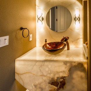 Удачное сочетание для дизайна помещения: туалет среднего размера в современном стиле с настольной раковиной, коричневыми стенами, столешницей из оникса, коричневым полом и разноцветной столешницей - самое интересное для вас