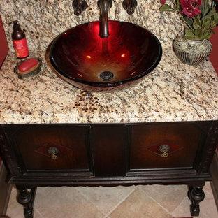 Immagine di un piccolo bagno di servizio classico con lavabo a bacinella, consolle stile comò, ante in legno bruno, top in granito, piastrelle beige, lastra di pietra, pareti rosse, pavimento in travertino e pavimento beige