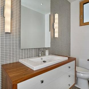 Ispirazione per un grande bagno di servizio design con lavabo a bacinella, ante lisce, ante bianche, top in legno, WC monopezzo, piastrelle grigie, piastrelle di vetro e pavimento in legno massello medio