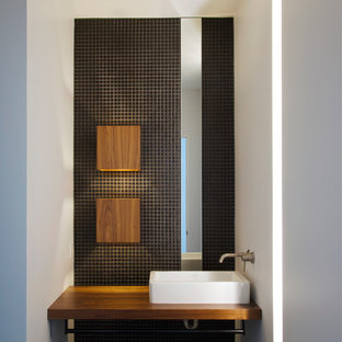 This is an example of a modern cloakroom in Kansas City with a vessel sink, wooden worktops, black tiles, mosaic tiles, white walls and brown worktops.
