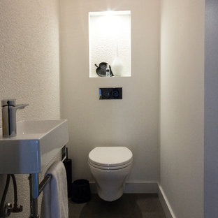 Modern cloakroom in Toronto with a wall mounted toilet, white walls, slate flooring, a wall-mounted sink and grey floors.