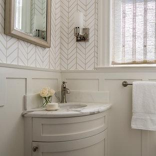 Exemple d'un WC et toilettes chic de taille moyenne avec un placard à porte shaker, des portes de placard beiges, un mur blanc, un lavabo encastré, un plan de toilette en marbre et un plan de toilette blanc.
