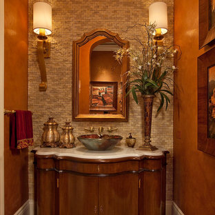 Inspiration for a mediterranean beige tile and stone tile powder room remodel in Miami with a vessel sink, dark wood cabinets and white countertops