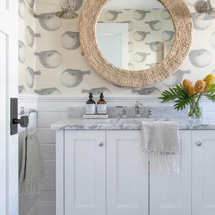 Modelo de aseo costero, grande, con armarios estilo shaker, puertas de armario blancas, paredes blancas, suelo de baldosas de cerámica, lavabo bajoencimera, encimera de mármol y suelo beige