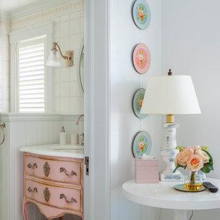 Shabby chic-inspirerad inredning av ett toalett, med ett undermonterad handfat, möbel-liknande, röda skåp, vit kakel och vita väggar