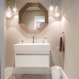 Inspiration for a mid-sized beach style white tile powder room remodel in Other with an integrated sink, flat-panel cabinets and gray walls