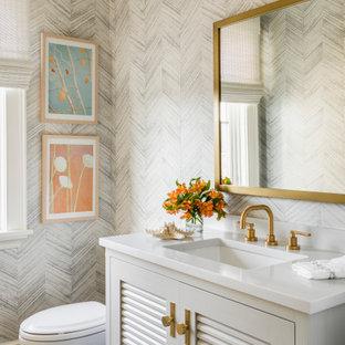 ニューヨークのビーチスタイルのおしゃれなトイレ・洗面所 (ルーバー扉のキャビネット、グレーのキャビネット、グレーの壁、アンダーカウンター洗面器、グレーの床、白い洗面カウンター) の写真