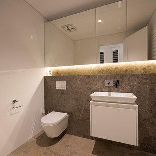 This is an example of a large modern cloakroom in Perth with white cabinets, a wall mounted toilet, multi-coloured tiles, stone tiles, white walls, slate flooring and solid surface worktops.