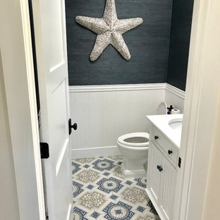 This is an example of a small nautical cloakroom in Miami with beaded cabinets, white cabinets, a two-piece toilet, multi-coloured tiles, ceramic tiles, grey walls, ceramic flooring, a submerged sink and multi-coloured floors.